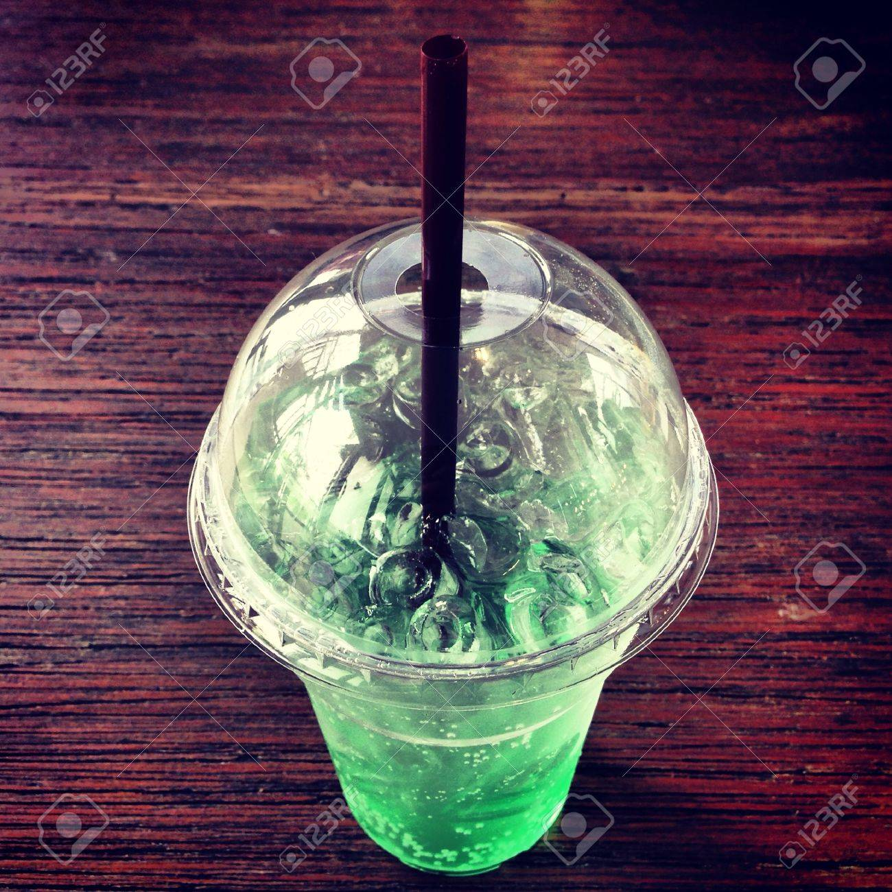 A glass of cold apple soda on the wooden table - 21480939
