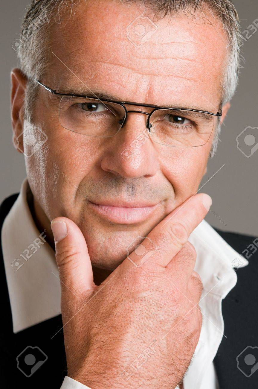 Confident pensive mature man with glasses looking at camera satisfied Stock Photo - 7889542