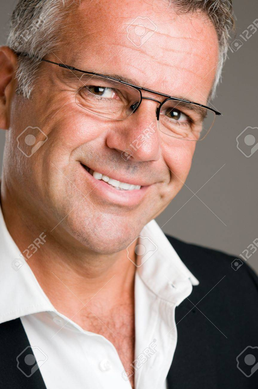 Smiling mature man looking at camera with a pair of glasses Stock Photo - 7889486