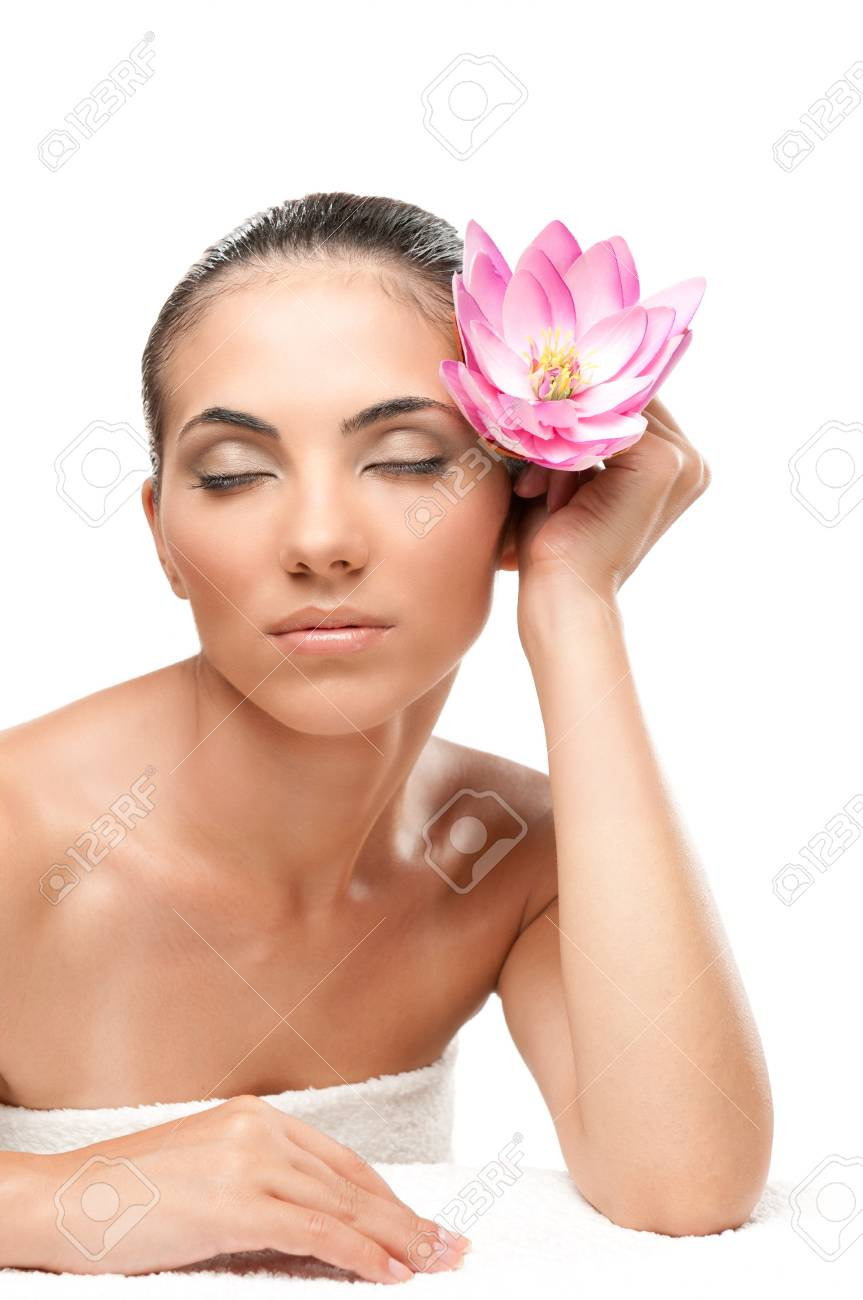 Beautiful young woman with lotus flower relaxing during a spa treatment isolated on white background, professional beauty makeup Stock Photo - 7889409
