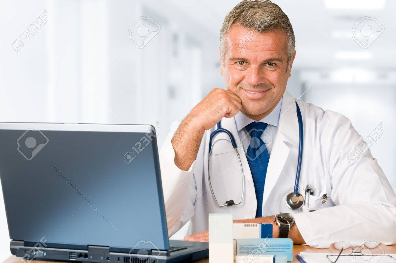 Happy satisfied mature doctor working and looking at camera in his modern clinic office Stock Photo - 7889577