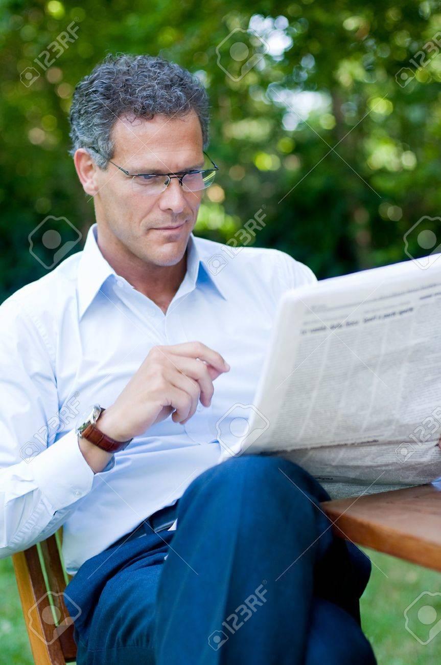 Mature man reading a newspaper outdoor Stock Photo - 8235296