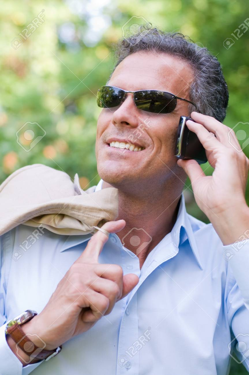 Smiling modern businessman talking on mobile outdoor Stock Photo - 8235218