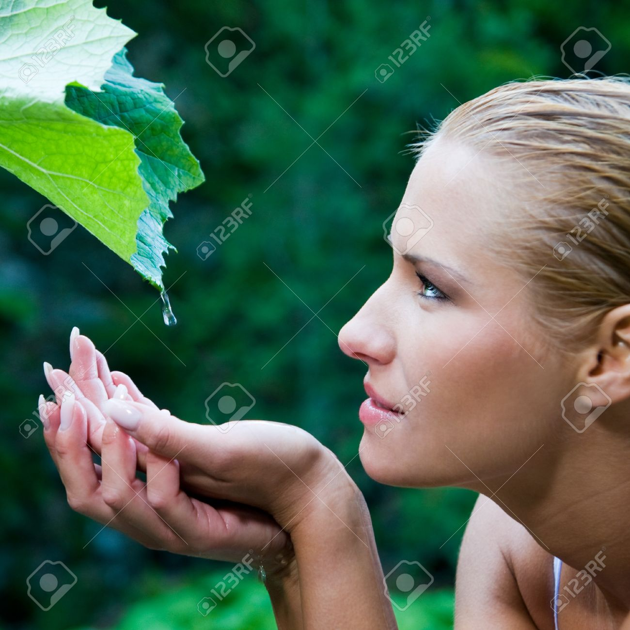 Beautiful young woman take a drop of clear water from a leaf in the nature. Symbol of purity, body care and nature harmony Stock Photo - 8235117