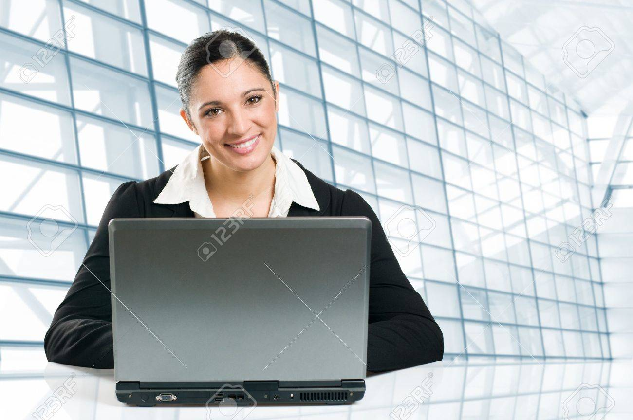 Young business woman typing on her laptop in a modern office Stock Photo - 8235196