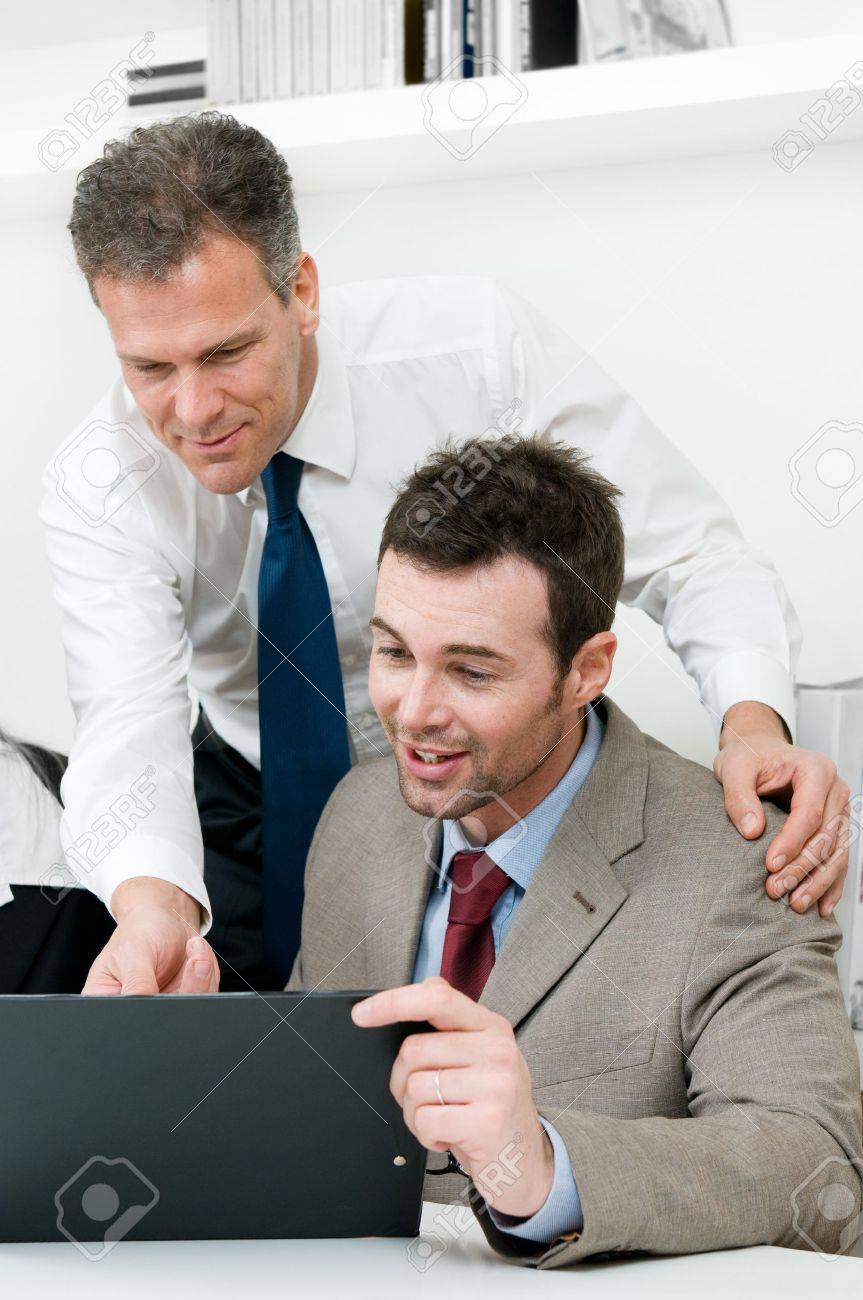 Mature manager looking at the work of his young colleague during a meeting in office Stock Photo - 8236146