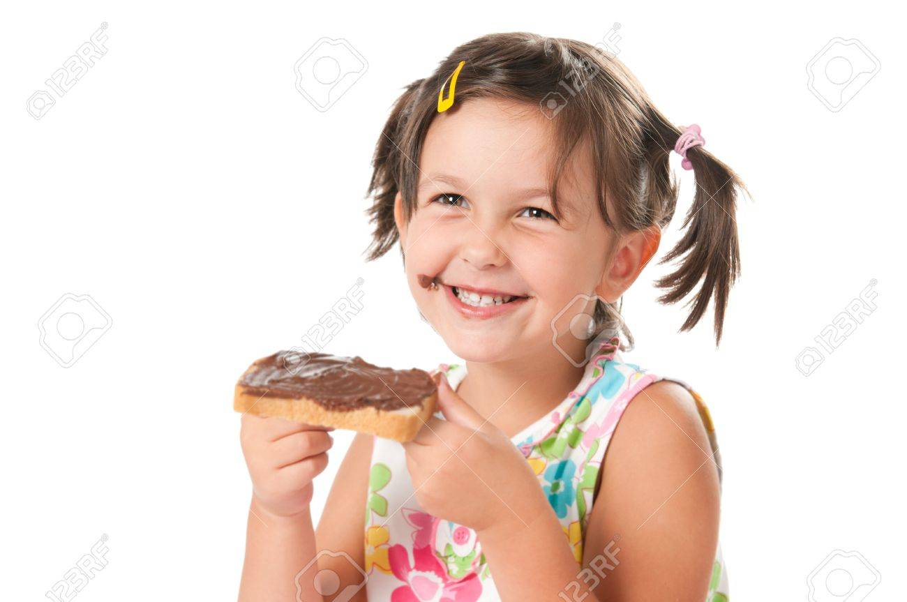 Happy smiling little girl biting a slice of bread with chocolate spread for snack isolated on white background Stock Photo - 8589868