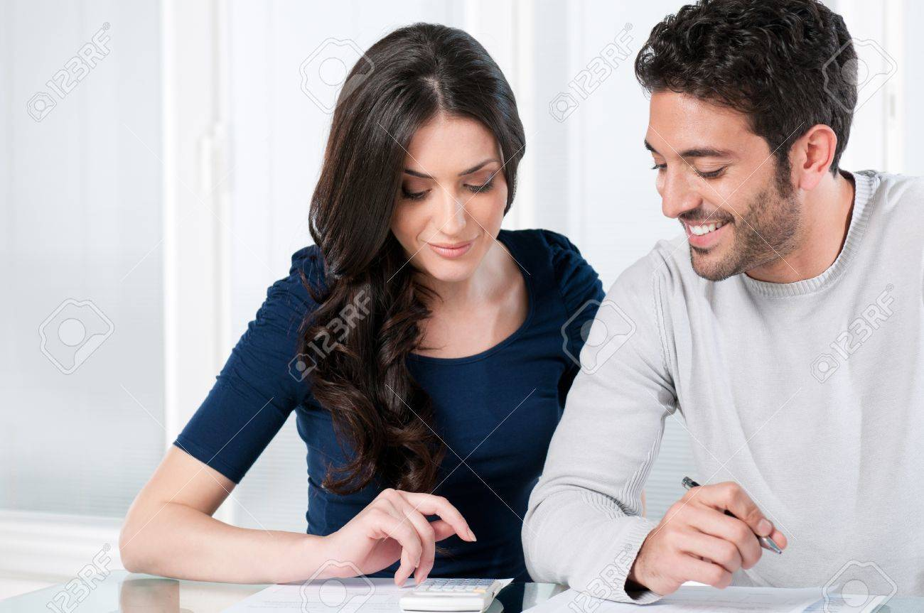 Happy smiling couple calculating their financial investments at home Stock Photo - 8590250
