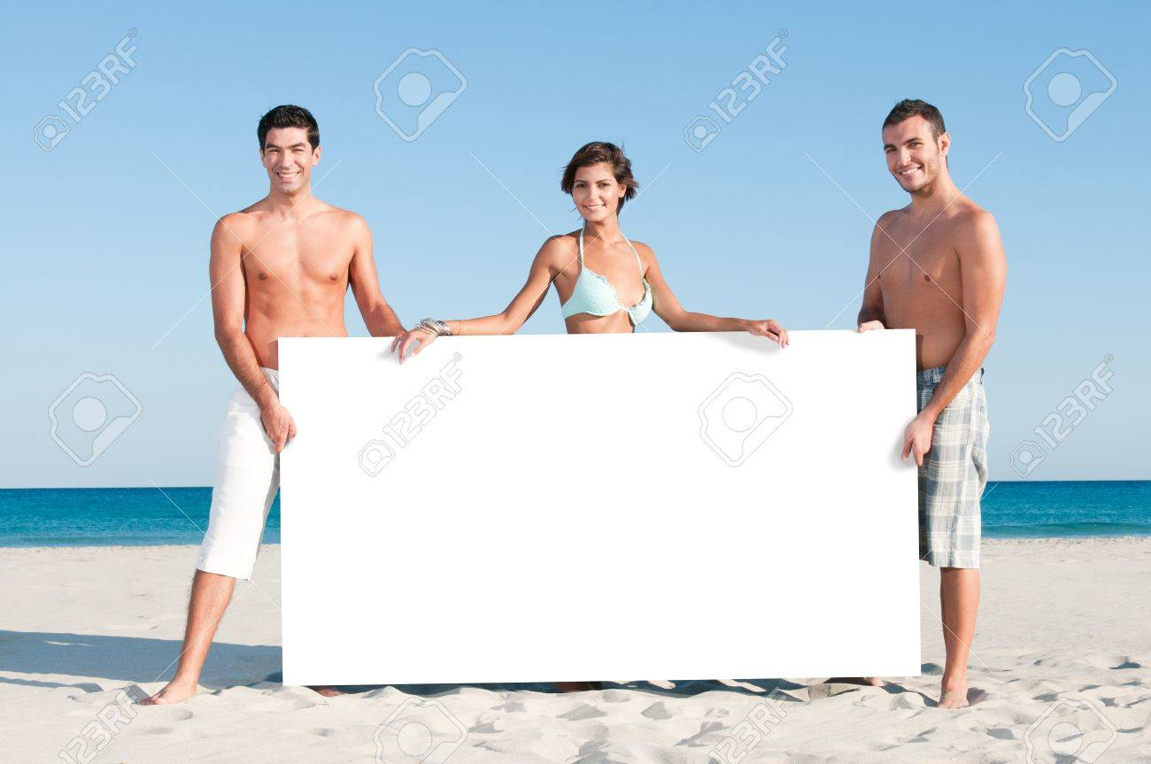 Happy smiling group of friends holding a white board for your text at summer beach Stock Photo - 8857064
