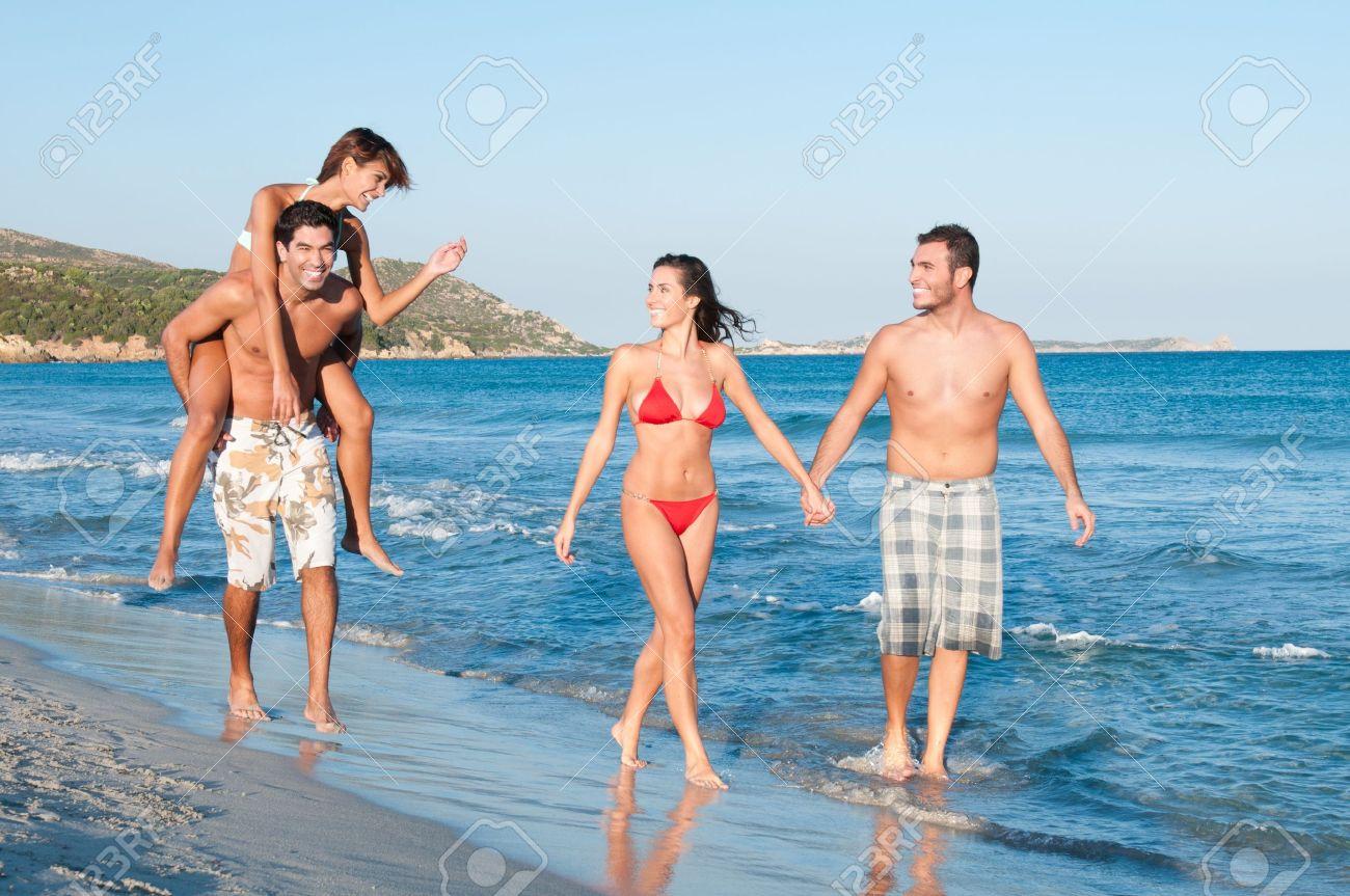Dos Parejas De Amigos Jugando Y Caminando Por La Playa En Un Dia De