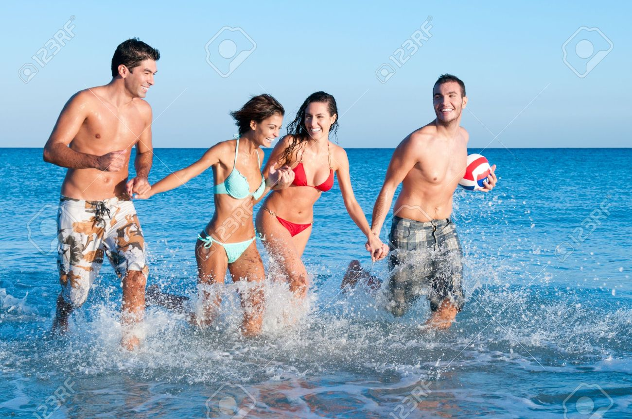 Happy couples of friends playing together and running in the water Stock Photo - 8857189