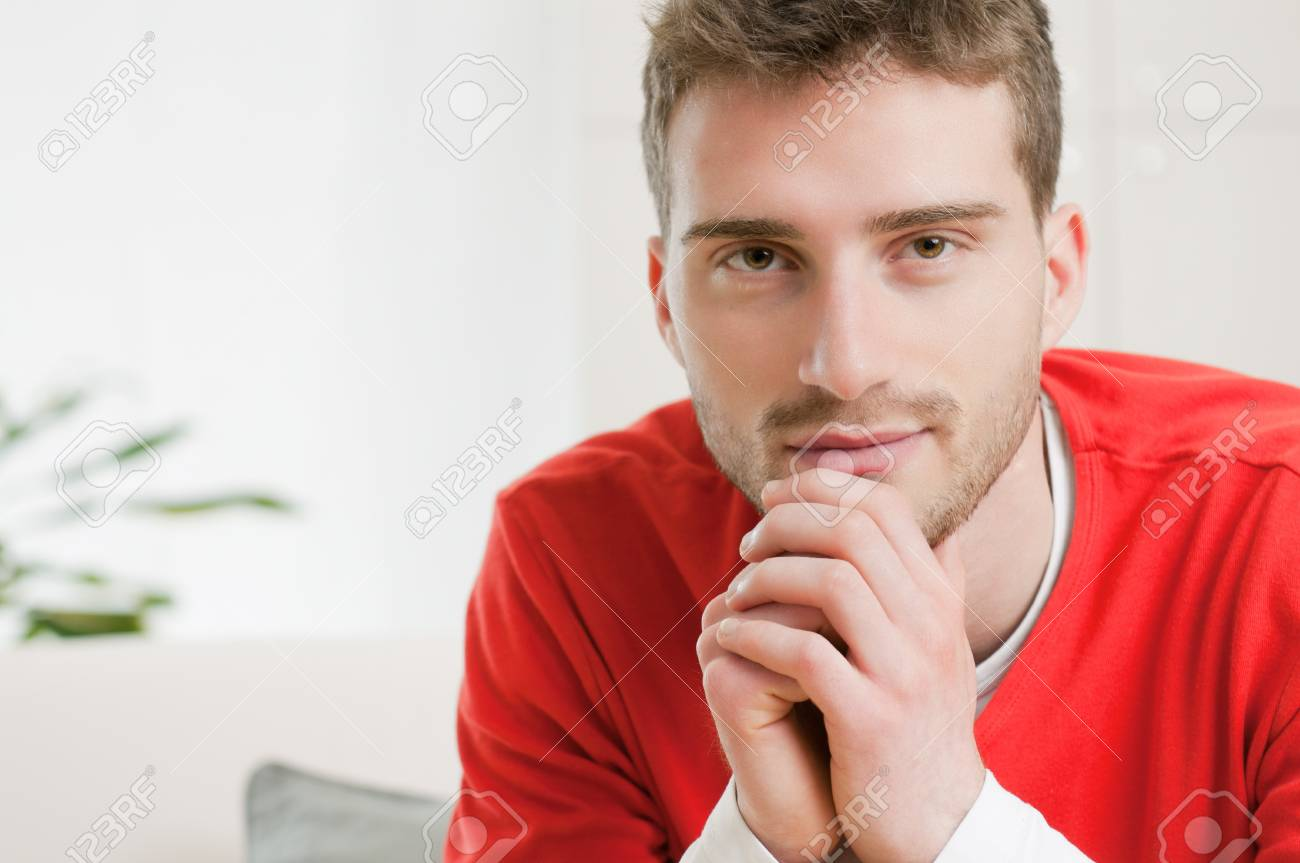Satisfied young man looking at camera at home Stock Photo - 9677685
