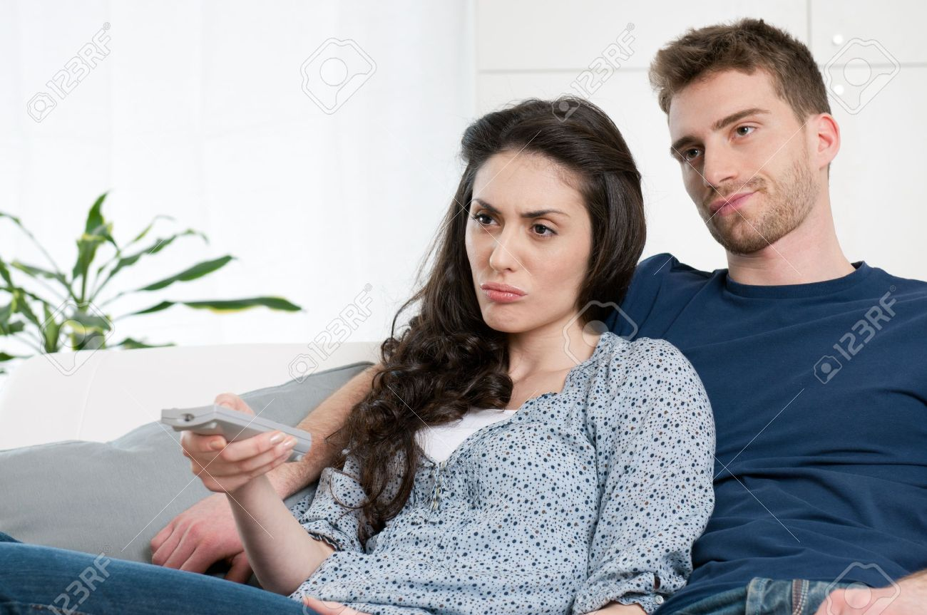 Bored Young Couple Watching Television At Home Stock Photo, Picture ...