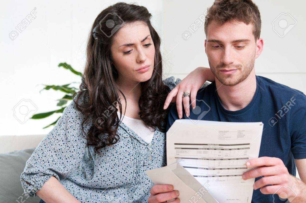 Young couple reading a financial bill or letter with worried expressions at home Stock Photo - 9677723