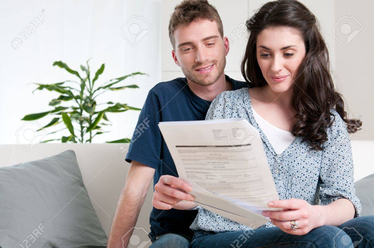 Smiling couple reading a bill arrived via mail Stock Photo - 9677721