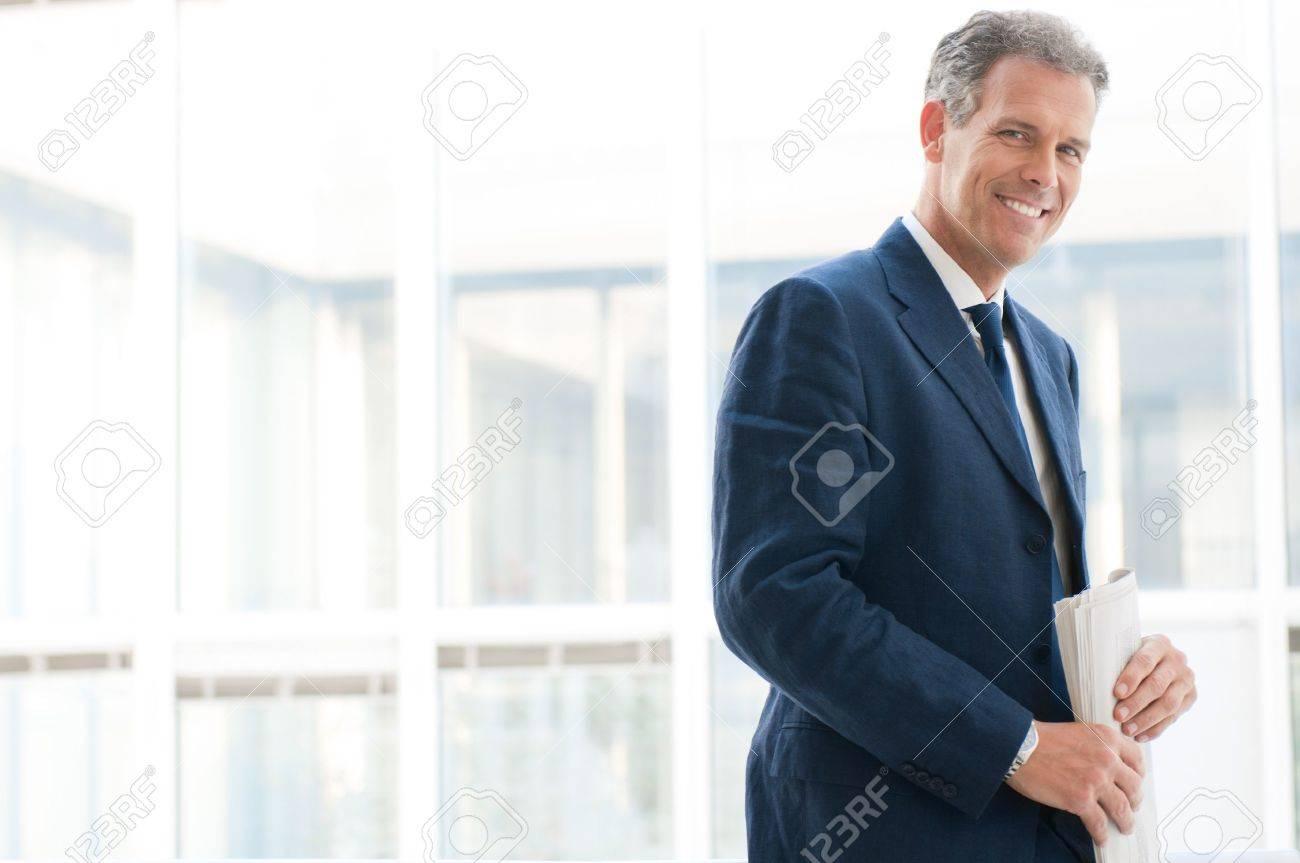 Smiling satisfied senior businessman looking at camera at office - 12669456
