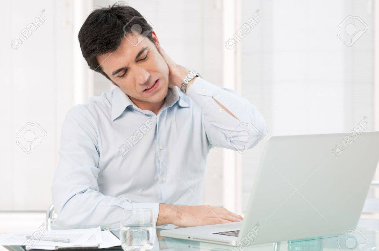 Businessman with neck pain after long hours at work Stock Photo - 13025697