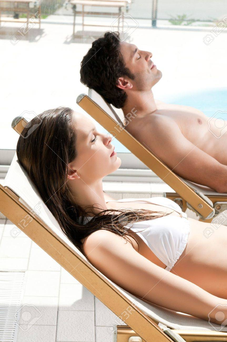 Relaxed couple sunbathing together at swimming pool in summer Stock Photo - 14486474
