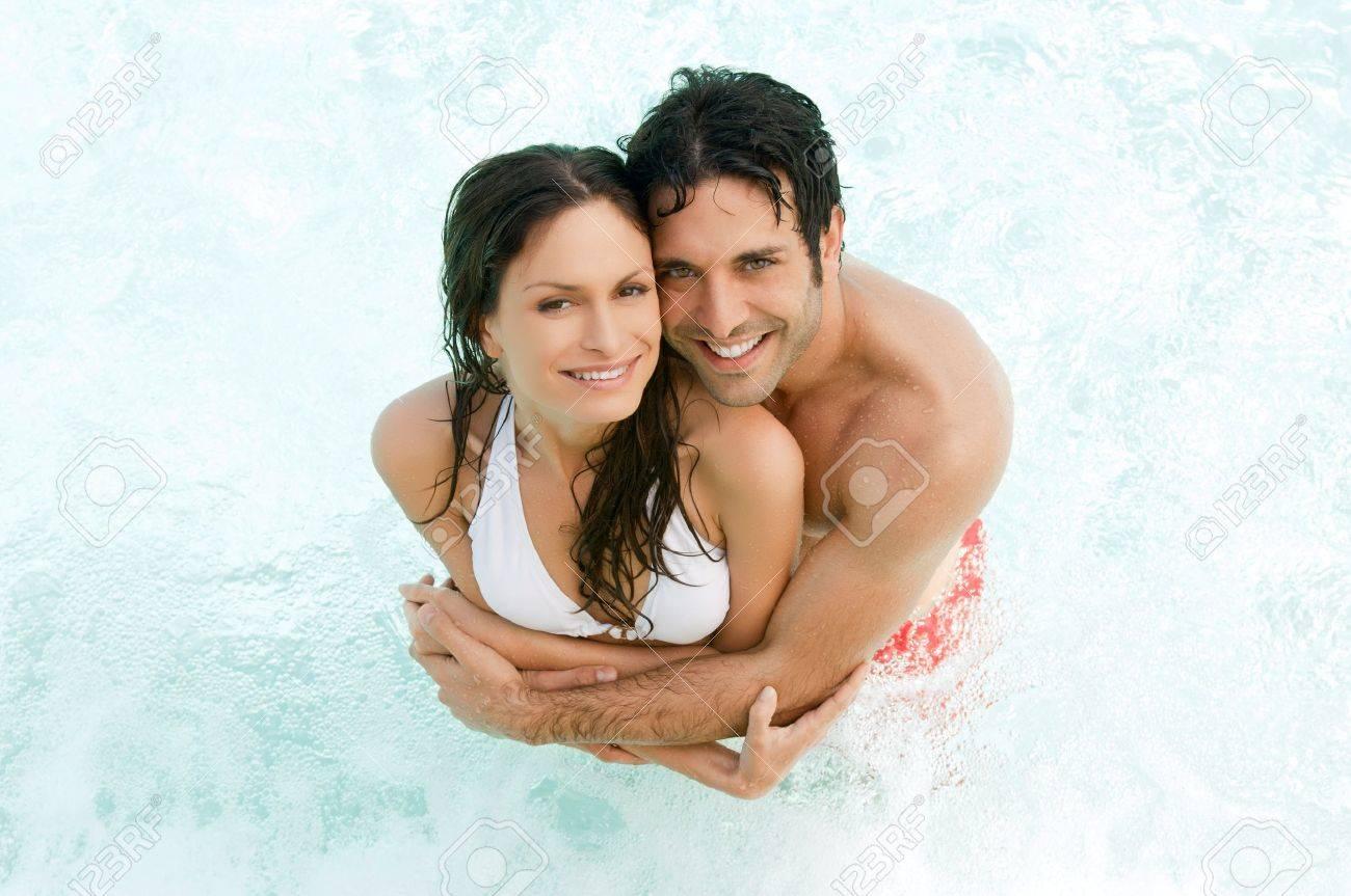 笑みを浮かべてカップルで抱き合うことで一緒に水に夏の高いビュー