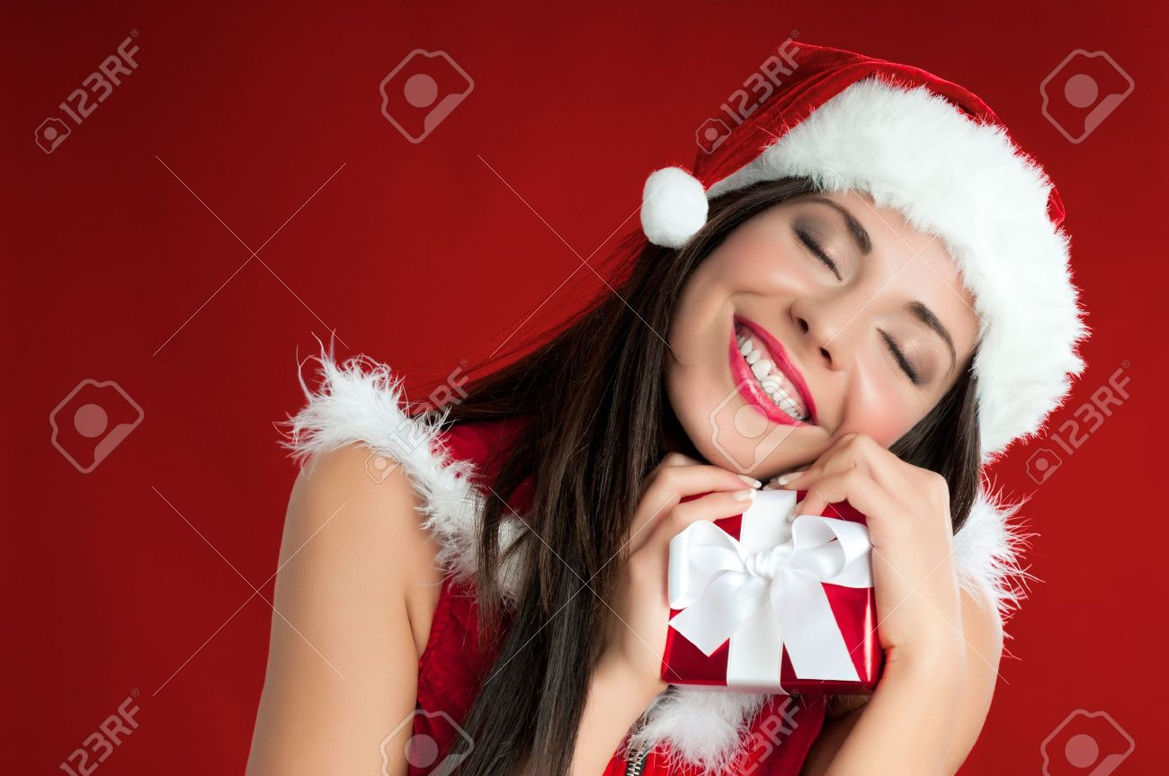 Happy smiling Santa girl holding a wrapped gift for Christmas Stock Photo - 15155137