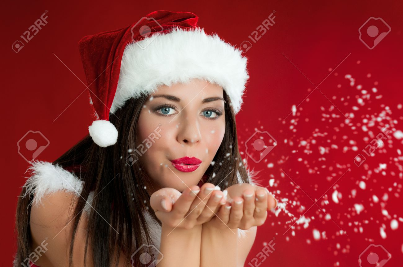Beautiful santa claus girl blowing white snowflakes from her hands on red christmas background Stock Photo - 15155152