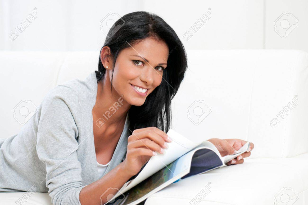 Smiling beautiful girl reading magazine and looking at camera at home Stock Photo - 16126494