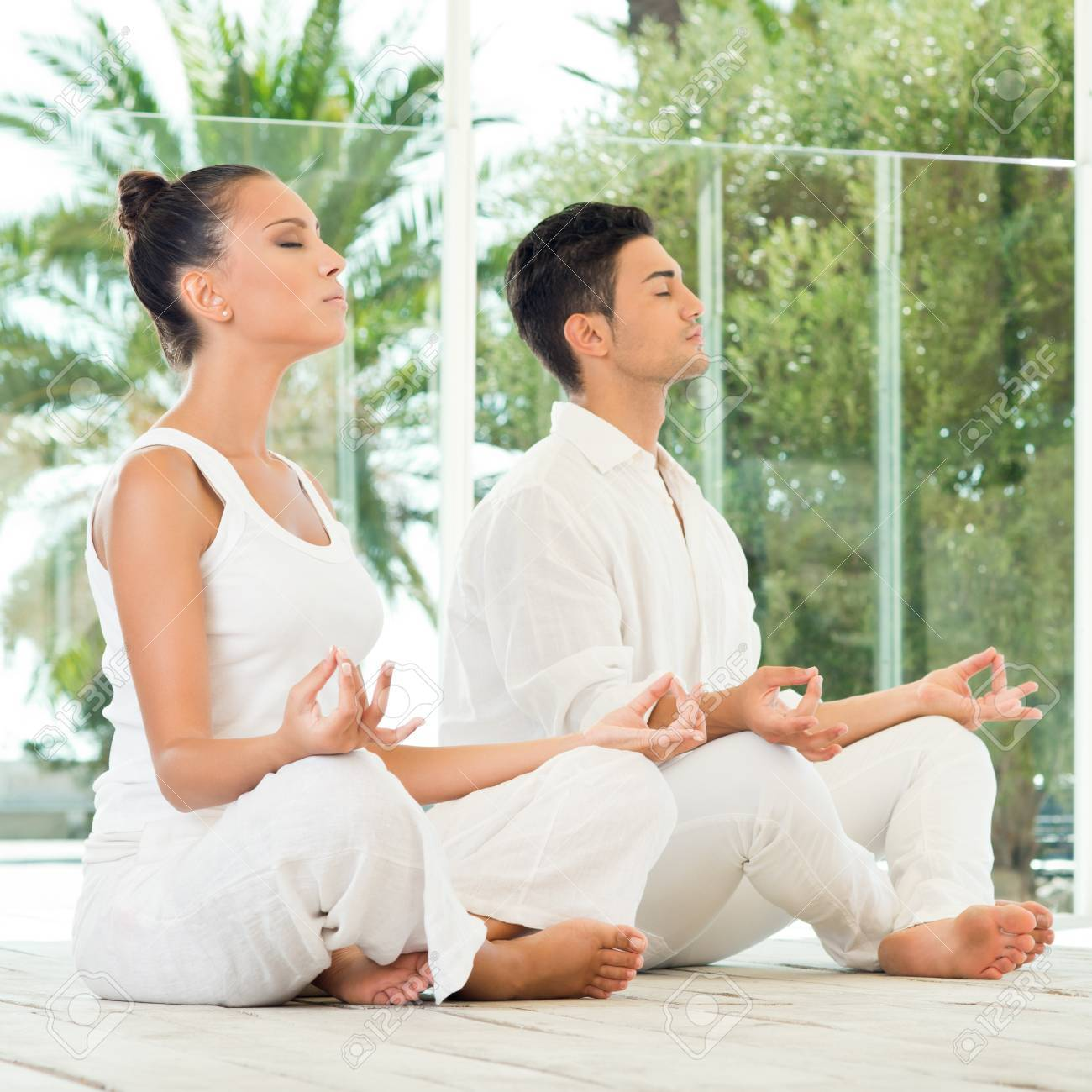 Young Couple Sitting In A Lotus Pose And Meditating Stock Photo - 16732497