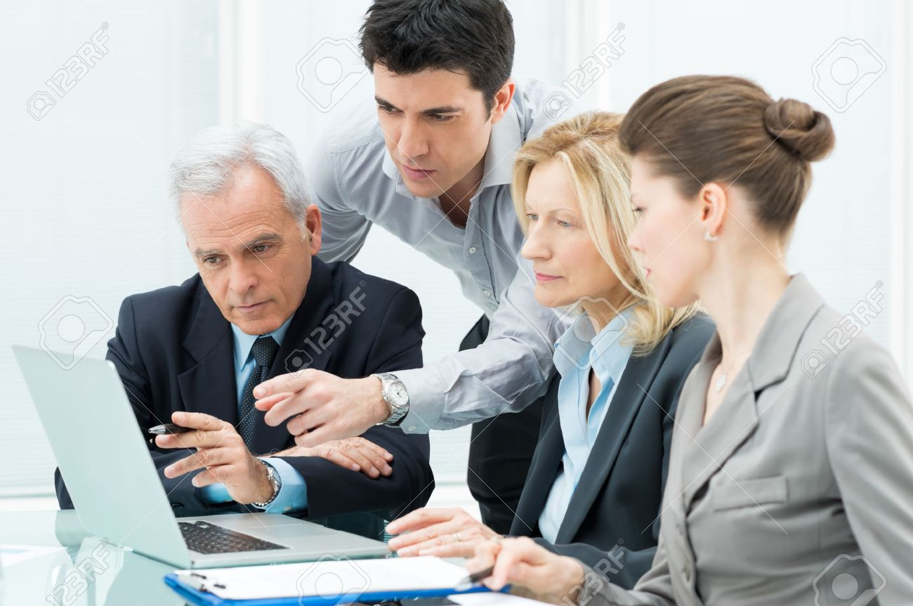 Team Of Business People Working Together On A Laptop Stock Photo - 19339117