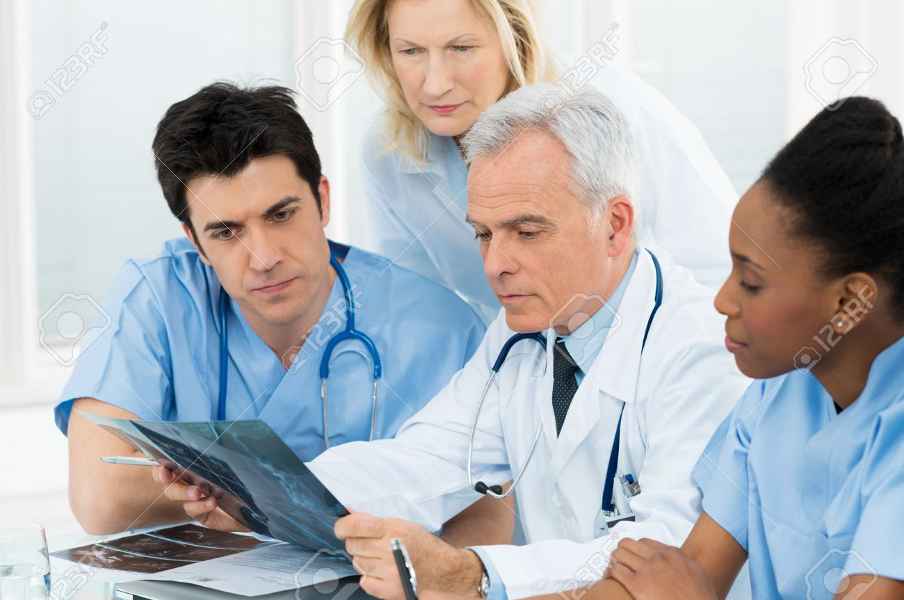 Team Of Experts Doctors Examining X-ray Report In Hospital Stock ...