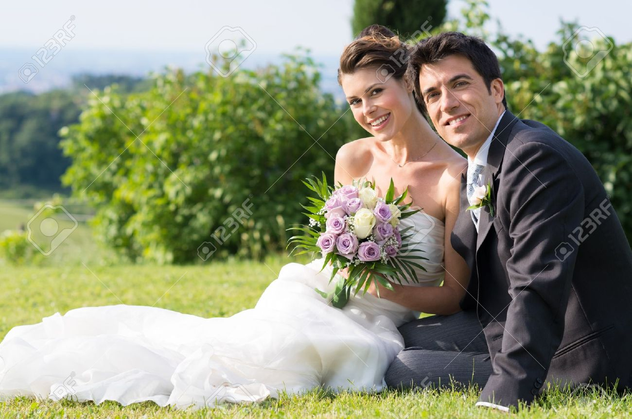 Portrait Of Happy Married Young Couple Sitting on Grass - 20838027