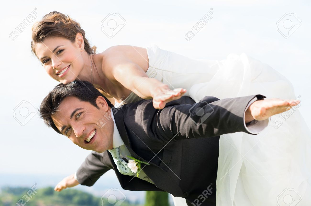 Happy Groom Giving Piggyback Ride To His Bride at Wedding Stock Photo - 20838030