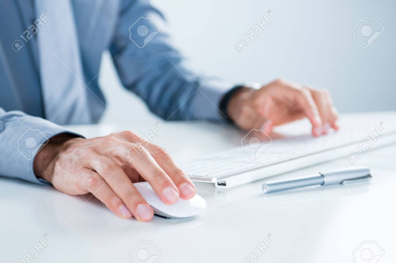 Close Up Of Businessman Using Computer At Desk In Office Stock Photo - 23338632
