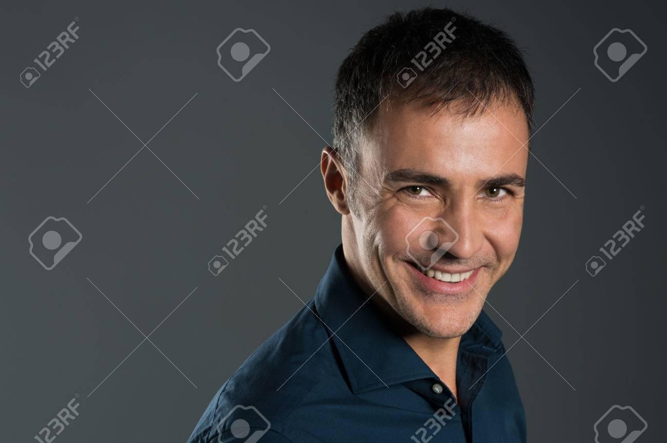 Portrait Of Confident Smiling Mature Man On Grey Stock Photo - 25271601