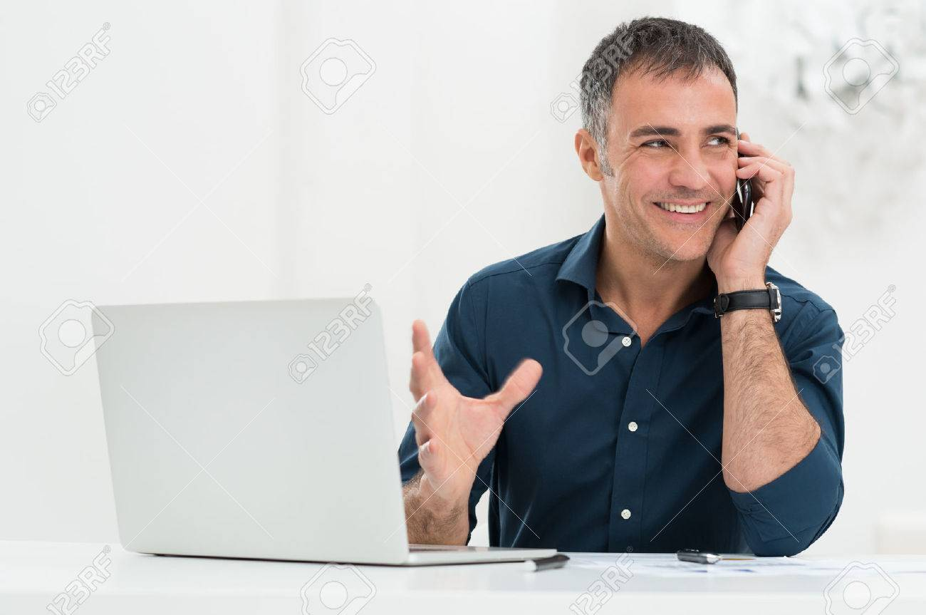 Portrait Of Happy Mature Man In Front Of Laptop Talking On Cellphone Stock Photo - 25271706