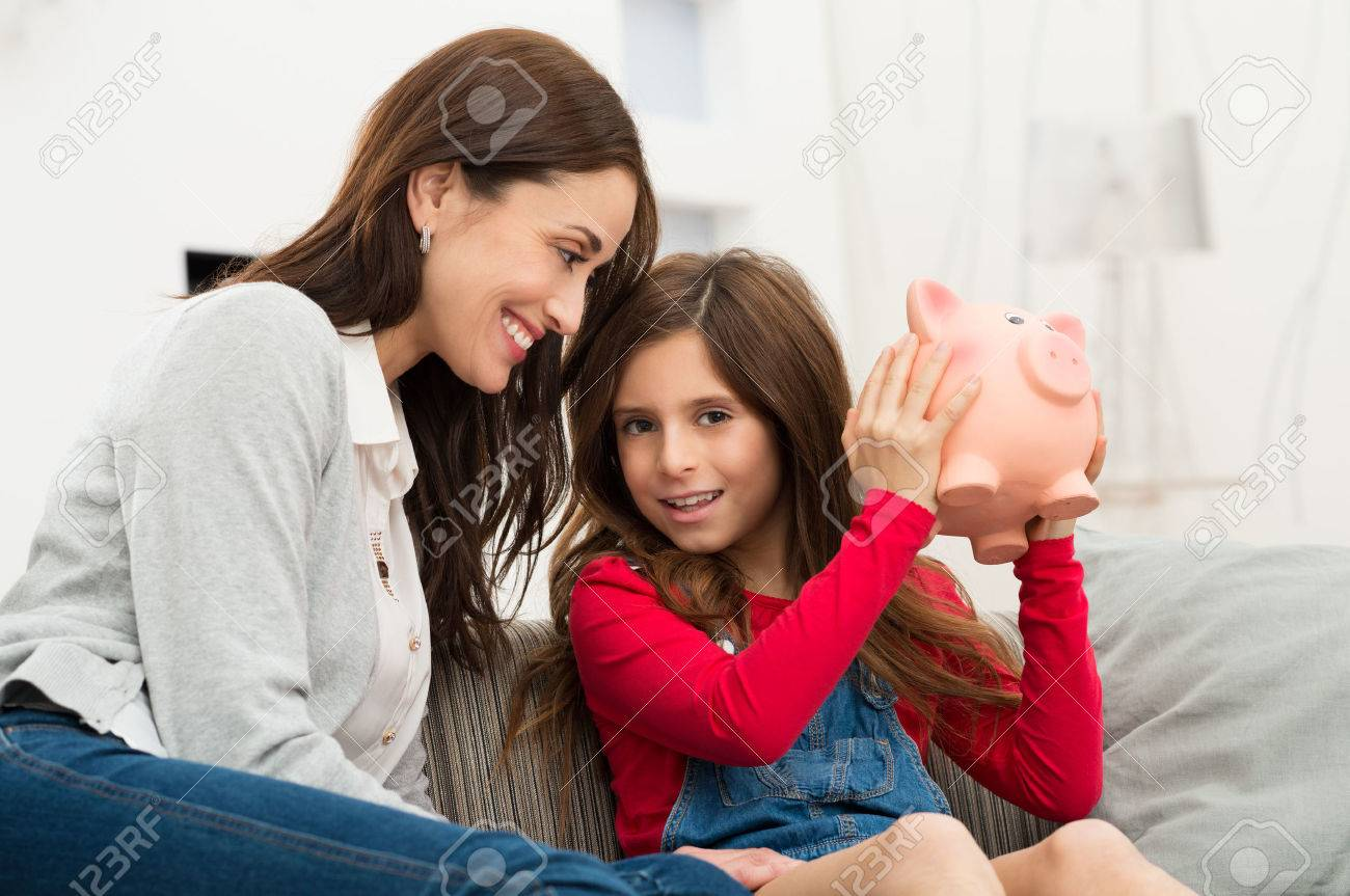 Smiling Mother Looking At Her Daughter Sitting On Couch Holding Piggybank Stock Photo - 25271992