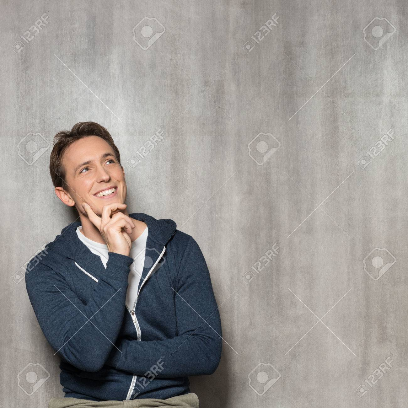 Young Happy Man In Blue Sweatshirt Thinking Stock Photo - 26825401