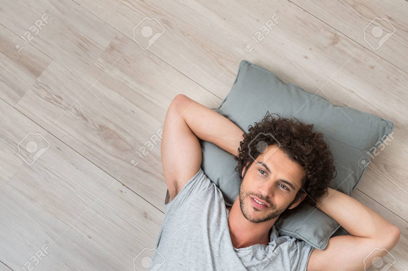 High Angle View Of Young Man Lying On Floor Thinking Stock Photo - 29862725