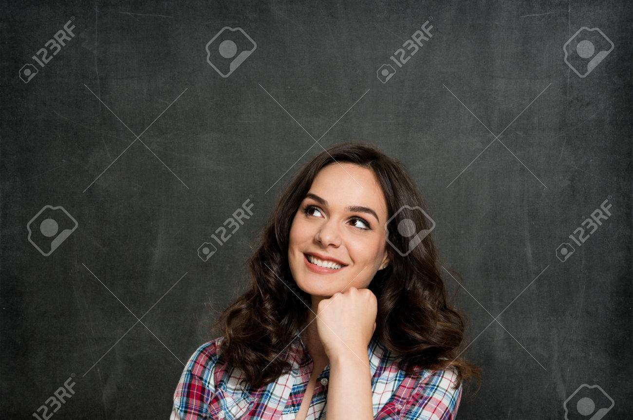 Happy Young Woman Contemplating Over Gray Background Stock Photo - 29862763