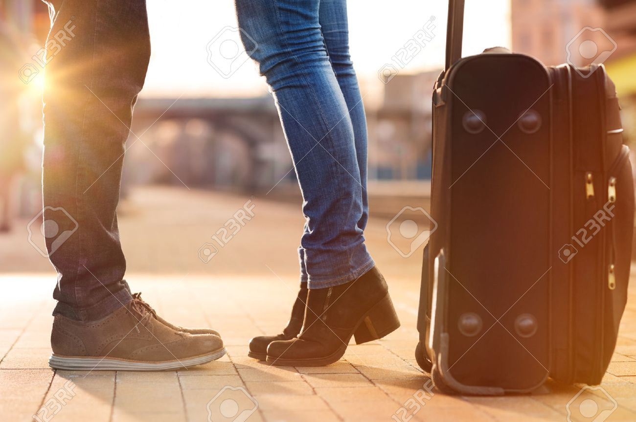 Closeup shot of woman feet standing on tiptoe while embracing her man at railway platform for a farewell before train departure. A travelling luggage is on the foreground. Beautiful warm sunset light and flare are coming from the background. Stock Photo - 38774790