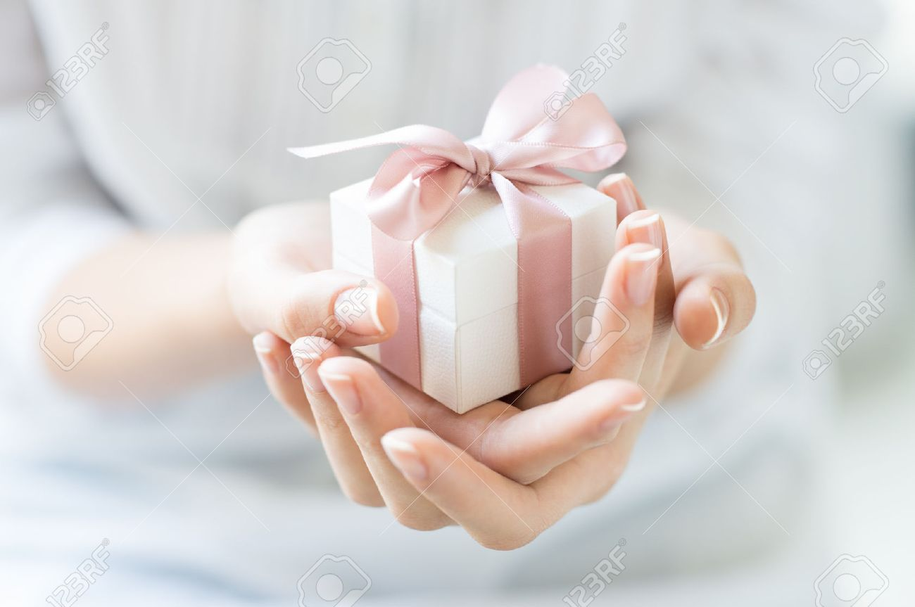 Close up shot of female hands holding a small gift wrapped with pink ribbon. Small gift in the hands of a woman indoor. Shallow depth of field with focus on the little box. Stock Photo - 41263307