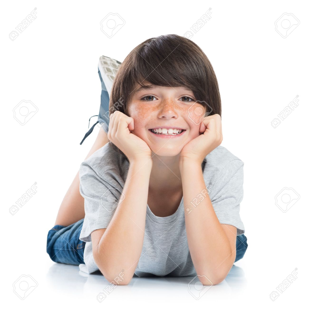 1d8c0e3b2a35 Closeup of smiling little boy with freckles lying on white background.  Happy cute male child lying on white floor and looking at camera.