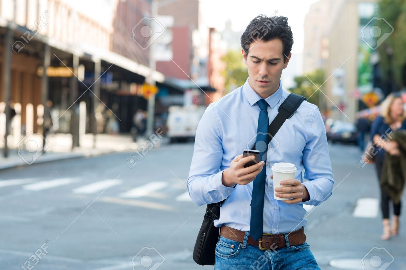 Businessman using smartphone and holding paper cup ina urban scene. Worried businessman in walking on the road and messaging with phone. Young man text messaging through cell phone while walking on the road in the city centre. - 50076694