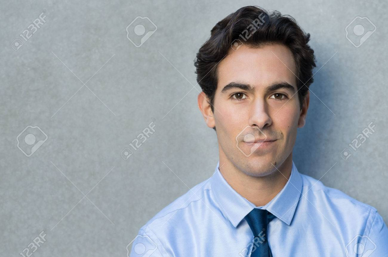 Happy young businessman leaning against grey wall. Portrait of a smirking businessman with blu shirt and tie looking at camera. Closeup of a handsome proud young man smiling with copy space. - 50076703