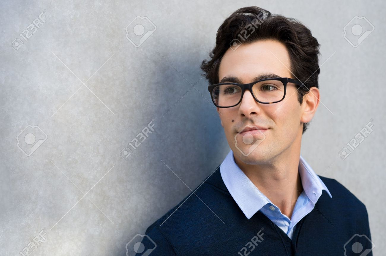 Smiling guy wearing glasses looking away and leaning on grey wall. Handsome young business man in casual wearing goggles and thinking. Portrait of young businessman with eyeglasses thinking about his carrer with copy space. - 50076788