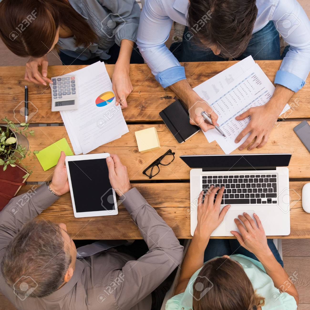 Businesspeople analyzing schemes and diagrams. Successful business people working with documents at the office. Group of businesspeople working together in office. - 51075196