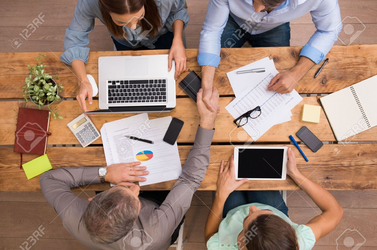 High angle view of businesspeople shaking hands and closing a deal. Successful business teamwork working at the office. Business partners sitting at table and planning work. - 51077858