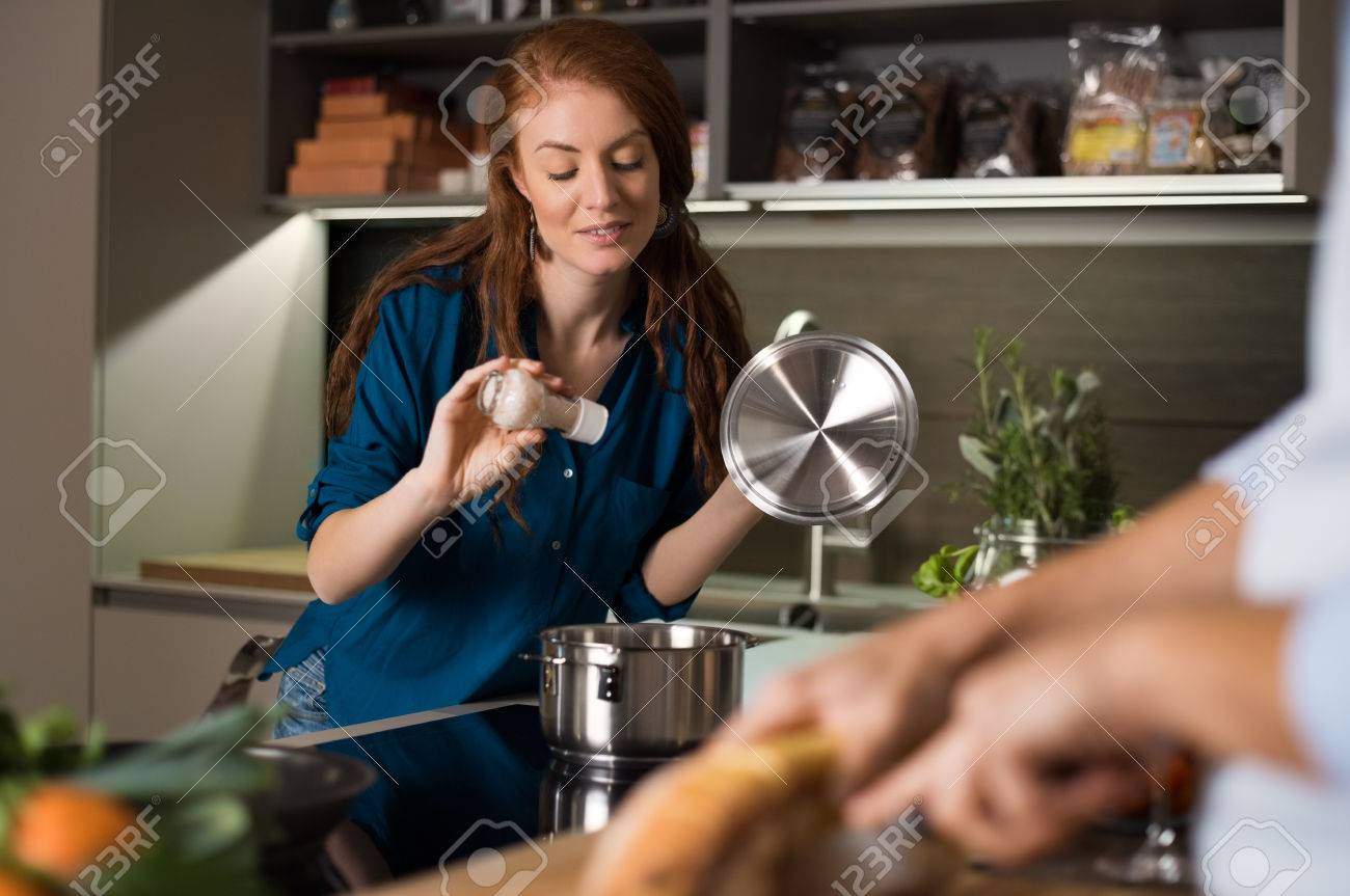 Happy young couple baking and cooking meal at kitchen. - 53492519