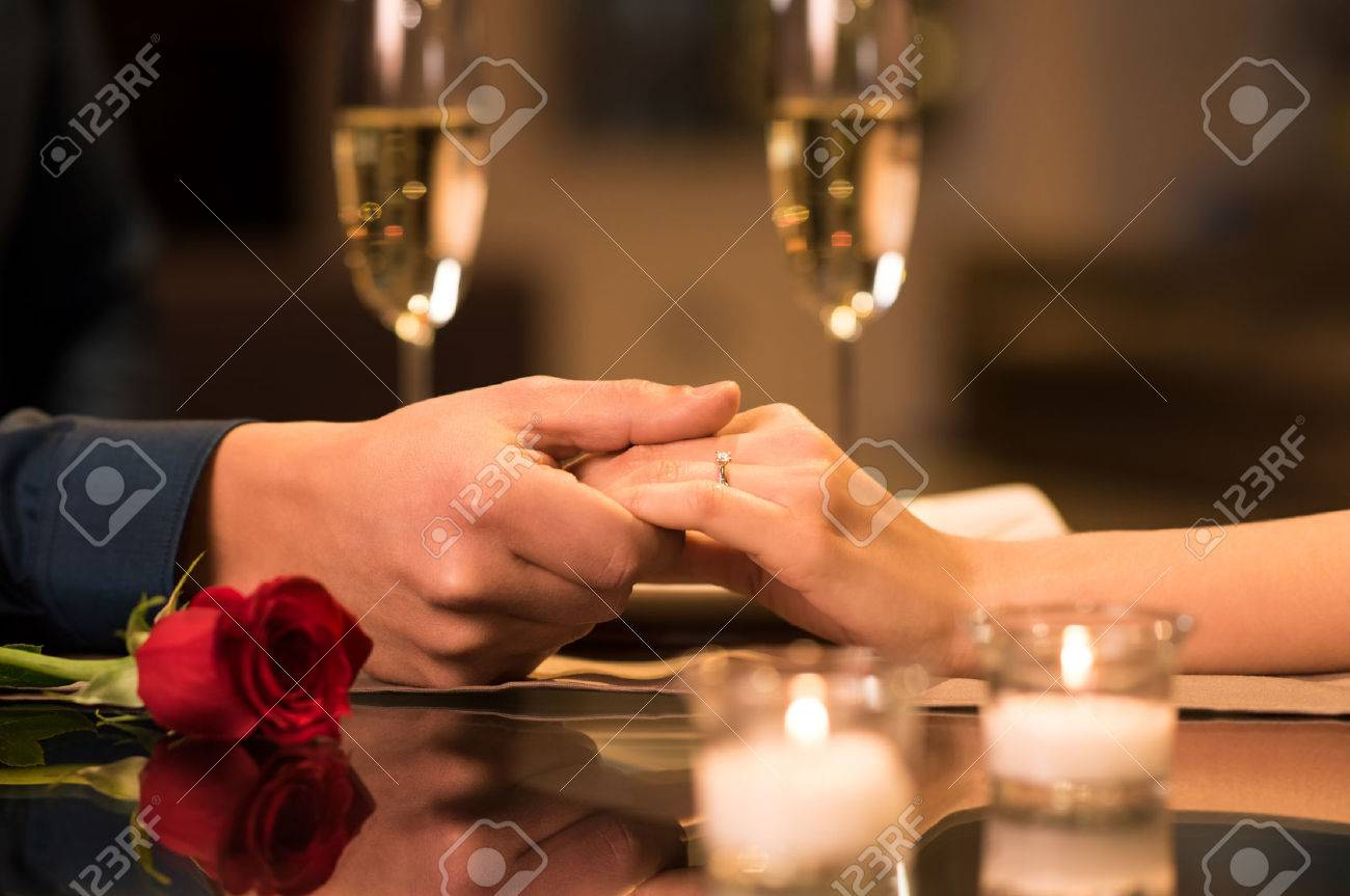 Closeup of couple hands on restaurant table with two glasses of champagne in background. - 53545506