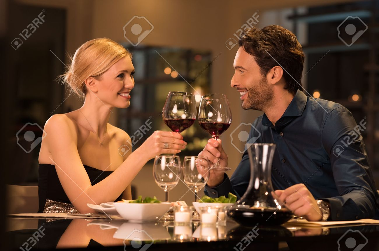 Couple toasting wine glasses during a romantic dinner in a gourmet restaurant. - 53545425