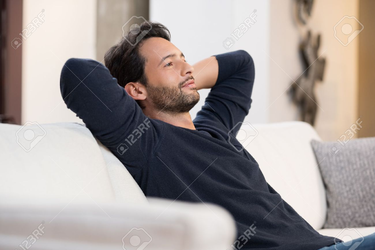 Handsome young man with hands behind head sitting on couch in living room. - 53545427